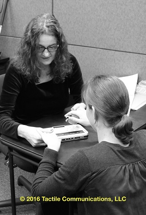 Image description: b&w picture of two women, Jelica and CJ. Both are at a small table; CJ's back is to the camera, while Jelica looking down, away from the camera. Jelica is showing CJ the braille notetaker; a device called, BSU2. *Image © 2016 by Tactile Communications, LLC