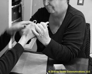 "Image description: b&w picture of a woman, Theresa, whom is wearing a black long sleeve top, using PT with another person whose face is not seen except for their hands (their nails are painted black). Theresa, pictured, is ""drawing"" a map on the person's hand.  *Image © 2016 by Tactile Communications, LLC"