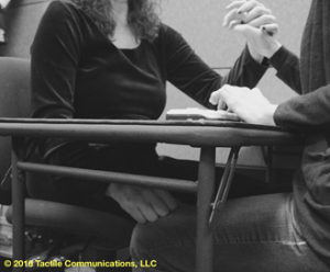 Image description: b&w picture of two people sitting at a table with a braille device, both wearing a black long sleeve shirt, and both are ProTactiling. The woman on the left, has her left hand on the person opposite of her, while her right hand is under the table, tapping (yes) on the person's knee. *Image © 2016 by Tactile Communications, LLC